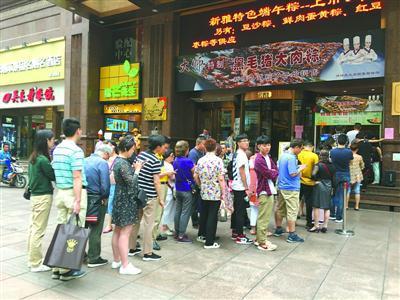 市民游客在新雅粤菜馆前排长队买粽子。裘雯涵 摄