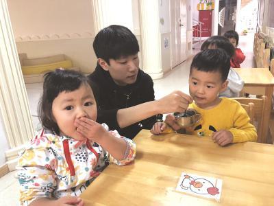 """新教师张宇成了孩子们喜欢的""""爸爸老师"""",经过几个月的锻炼,他已经可以熟练地给孩子们喂饭。本报记者张鹏摄"""