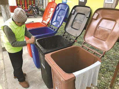 """每天下午4点半,黄国祥准时把4个垃圾箱从仓库拉出来,擦洗干净,迎接""""顾客""""的到来。 均殷梦昊 摄"""
