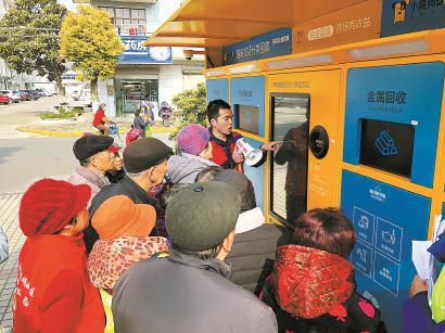 """3月5日学雷锋活动中,年轻志愿者郭旭程在指导老年居民们如何使用""""小黄狗""""智能回收机。"""