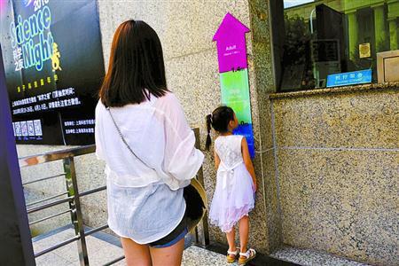 上海海洋水族馆售票处,一位家长让孩子主动到标尺下量身高,确认无误后再买票。黄尖尖 摄