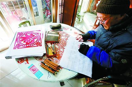 朱金辉老人正在伏案创作剪纸。姜辉辉 摄