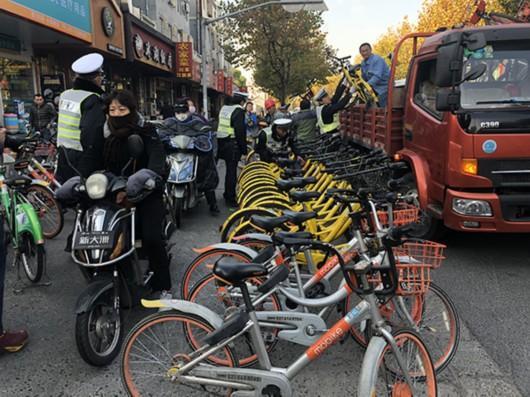 图片说明:工作人员正在清理违停共享单车。