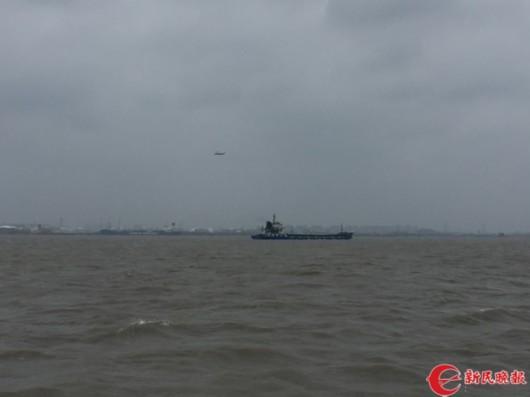 图片说明:上海海事的救助直升机一直在事发锚地上空盘旋搜救 曹刚 摄