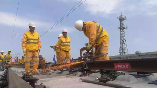 施工人员对最后一对长钢轨进行焊接打磨
