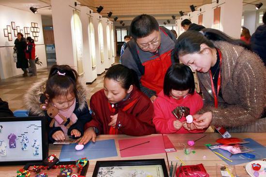 3月10日,在上海市黄浦区教育学院附属中山学校举行的校园开放日活动上,两名幼升小儿童在家长的带领下,正在跟该校师生学习手工。张锁庆 摄