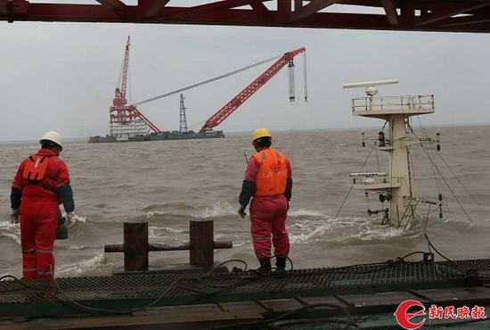 图说:打捞船正在沉船旁全力搜救 来源/新民晚报记者陈梦泽 摄