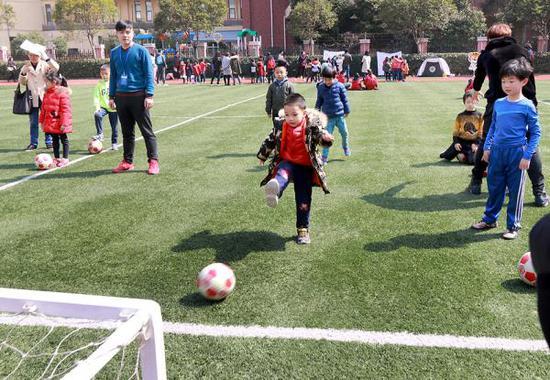 3月10日,在上海市浦明师范学校附属小学举行的校园开放日活动上,一名幼升小儿童在该校师生的辅导下练习踢球射门。张锁庆 摄