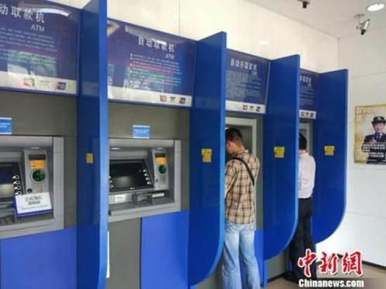 图说:民众在自动取款机上取钱。中新网记者 李金磊 摄