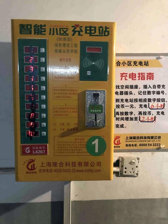 △图为小区安装的智能充电站,上面标有操作说明和收费,左侧按钮被居民泼上了黑漆。