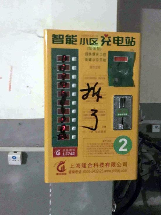 """△充电站按钮被涂抹上了一层黑漆,还写上了""""拆了""""二字。"""