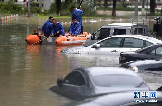 8月10日,人们乘坐橡皮艇经过温岭市太平街道路边被水淹的汽车。新华社记者 韩传号 摄