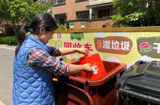 """居民正在""""绿色专列""""边投放垃圾。闵行区浦锦街道 供图"""
