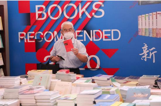 8月13日,一名读者在书展上挑选书籍。新华社记者 方喆 摄