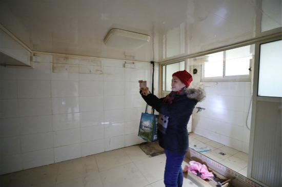 图说:居民丁阿姨在已搬空的房内拍照留念。 本报记者 周馨 摄