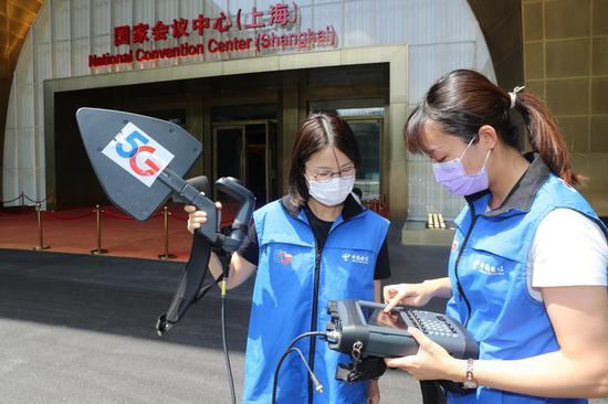 在进博会主会场门口,上海电信移动互联网部的员工正在优化5G信号。王万隆摄影
