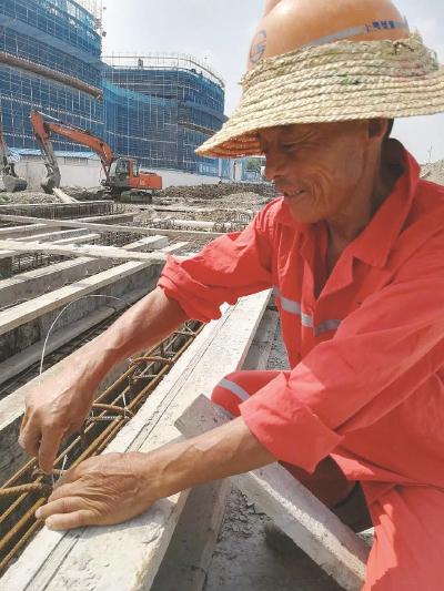 整个工程中,最辛苦的要数钢筋工和模板工,项目中有三座桥梁施工,浇筑钢筋混凝土时,要确保在混凝土干掉前把扎钢筋、做模板的活跟着现场进度干完,一般两三个小时活都不能停,大的结构有时还需要连续作战五六个小时。图为浇筑混凝土前,工人在烈日下徒手扎牢钢筋。周振摄