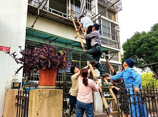 图说:保安队长王耀平爬上扶梯,紧紧托住老人身体