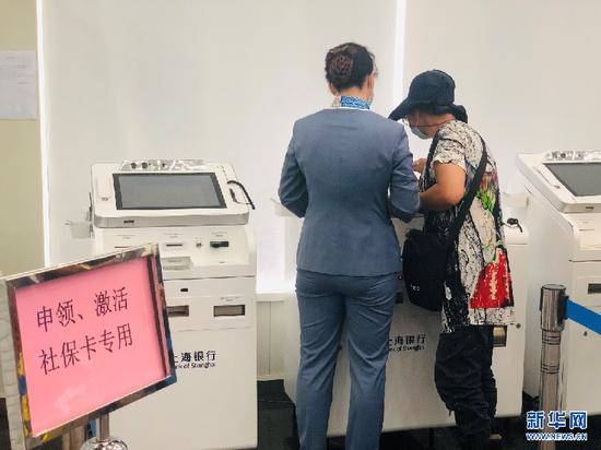 图为市民在上海银行临汾路支行工作人员帮助下换领新社保卡。新华网 李硕摄