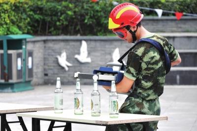 图为消防员展示液压钳夹乒乓球技能 谢智君摄