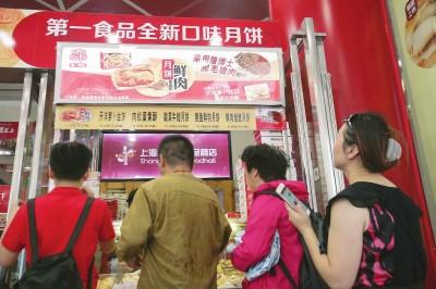 """一家""""老字号""""新推酸菜牛蛙、鲍鱼鲜肉和鲜肉焙熄等口味的月饼,引来不少顾客排队购买。本报记者叶辰亮摄"""