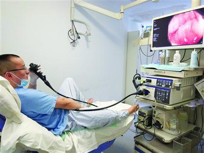 """冯卓左手控制着肠镜的大小旋钮,右手握着镜子前进和旋转,床前的显示器正现场""""直播""""肠内情况。 /医生供图"""