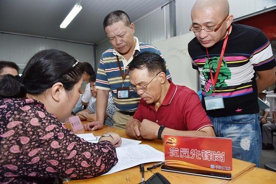图说:工作人员在签约现场回答居民疑问。陈泰明 摄
