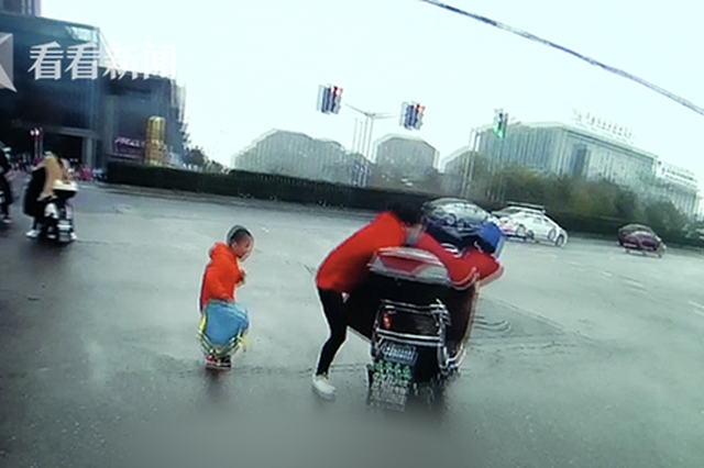女子骑车送娃上学不慎滑倒 交警熟练抱娃当奶爸
