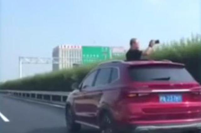 沪一SUV高速上龟速行驶 车内男子探出天窗拍照