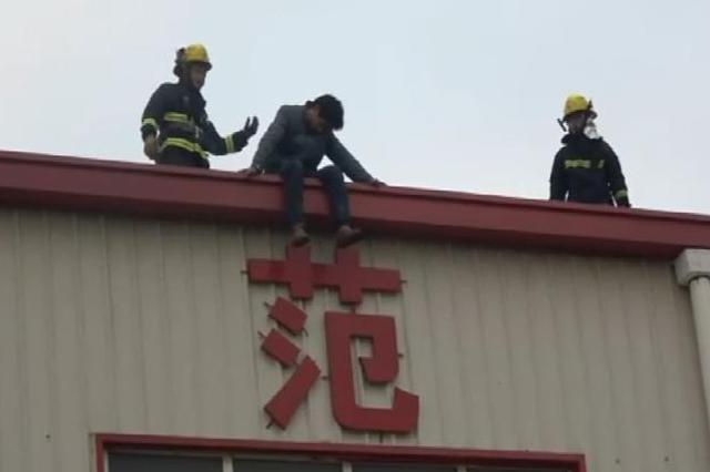 40岁男子坐楼顶边缘意识模糊 沪消防队员喊话间隙救人