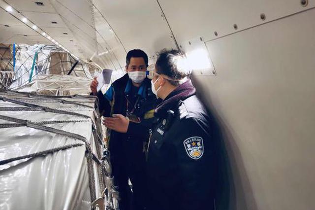 沪边检平易近警雨中候机保障通关 载运53箱口罩公事机入境