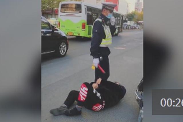 上海一男子逆行闯红灯还躺地抱辅警大腿 污蔑其打人
