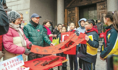 火红的春联为义卖现场带来了浓浓的年味。本报见习记者 孟雨涵 摄
