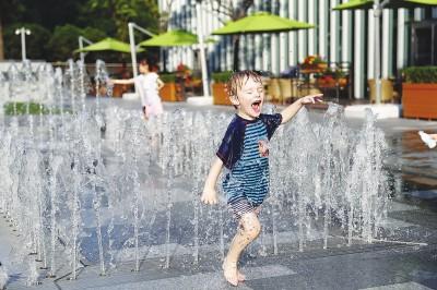 小朋友们在喷泉嬉戏,解暑降温。本报记者袁婧摄
