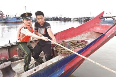 三甲港边防派出所警官协助渔民加固捆绑渔船,做好抗击大风大雨的准备工作。本报记者赵立荣摄