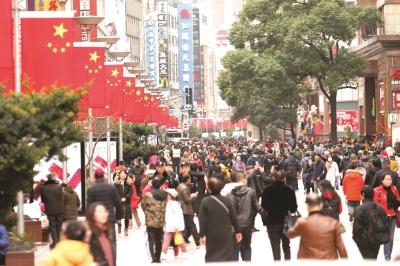 南京路步行街上,红旗随风飘扬,与熙熙攘攘的游人相映成趣。本报记者叶辰亮摄