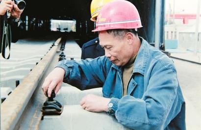 钱崇鑑拧紧青藏铁路新线第一节轨道上的一颗螺丝钉。