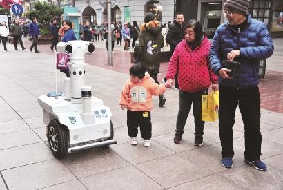 警用巡逻机器人出现在南京路步行街,不时提醒市民注意街面防盗,这让一对带着孙女逛街的老夫妇感到很新鲜 杨建正摄