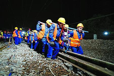 施工人员正将25米长的钢轨移到指定位置。