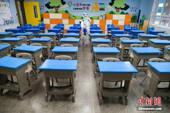 2月28日,山西省太原市,防疫消杀人员正在对新建路小学教室进行消杀作业,为新学期做准备。 中新社记者 张云 摄