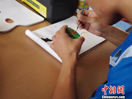 在教育矫正中心,学员们正在木质小玩具上专心地绘制图案 范丽芳 摄