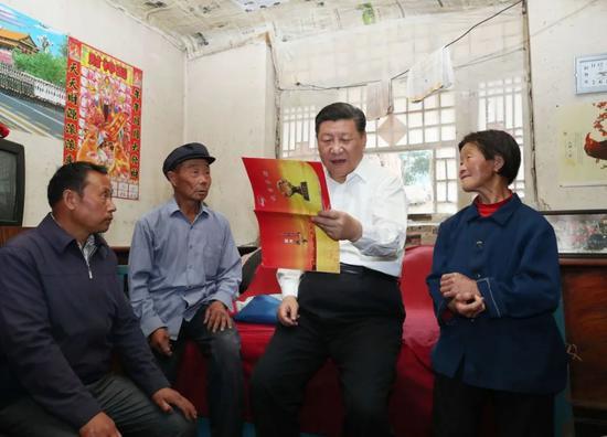 2017年,习近平在赵家洼村特困户刘福有家中察看扶贫手册。新华社记者 庞兴雷 摄