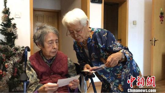 """""""唠嗑队""""成员(右一)正在陪孙毓黎看照片。 李庭耀 摄"""