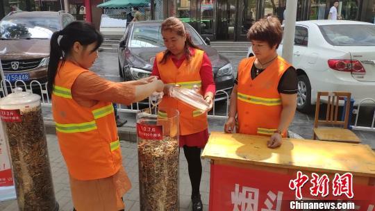 """长治市潞州区环卫处开展""""烟头不落地、城市更美丽""""环保宣传活动,集中展示""""清理烟头专项治理行动""""开展以来的清理成果。 冯嘉伟 摄"""