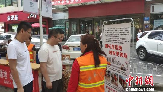 宣传现场用玻璃罐展示环卫工人每天清扫过程中收集到的烟头,并有环卫工人向路过的群众进行讲解。 冯嘉伟 摄