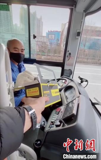 太原海归青年刘文奇将自己在网上购买的口罩送给公交车司机。受访者供图