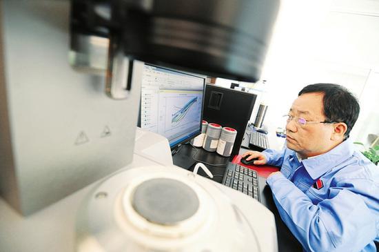 吕春祥在实验室分析测试数据(资料图)。