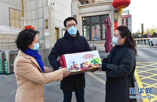 """2月10日,太原市妇联的工作人员将""""暖心包""""送给支援武汉医疗队队员段淑琴的家属(左二)。"""