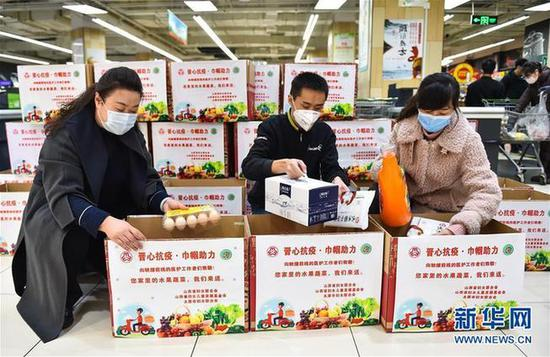 """2月10日,在太原市永辉超市,工作人员将生活物资放入""""暖心包""""。新华社发(柴婷 摄)"""