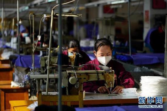 在山西省太原市的太原白鸽服装有限责任公司,员工在加紧生产口罩(2月13日摄)。新华社记者 詹彦 摄